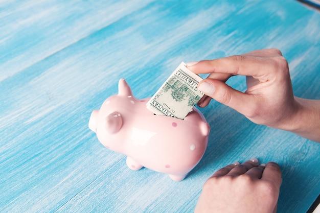 Mulher jovem joga um dólar em um cofrinho enquanto está sentada em frente à mesa