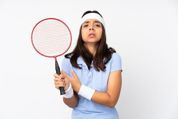 Mulher jovem jogador de badminton sobre fundo branco isolado congelando