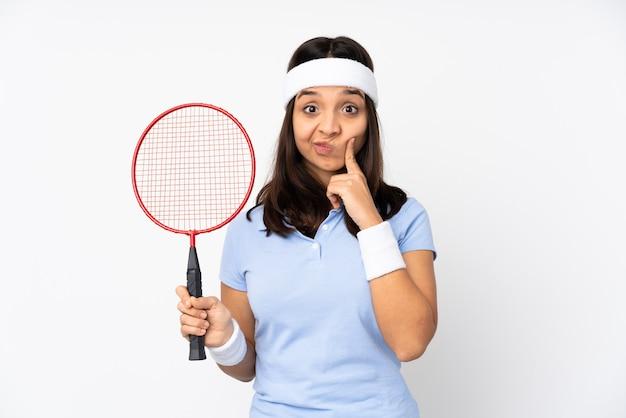 Mulher jovem jogador de badminton sobre fundo branco isolado e olhando para a frente