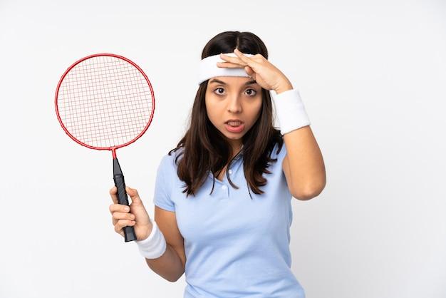 Mulher jovem jogador de badminton sobre fundo branco isolado olhando para longe com a mão para olhar algo