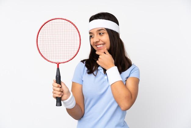 Mulher jovem jogador de badminton sobre fundo branco isolado olhando para o lado