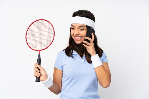 Mulher jovem jogador de badminton sobre fundo branco isolado segurando café para levar e um celular