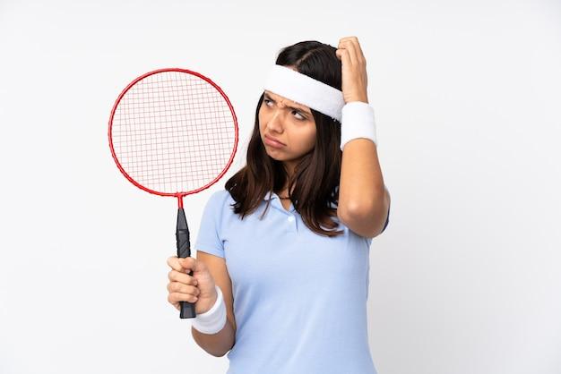Mulher jovem jogador de badminton sobre fundo branco isolado tendo dúvidas enquanto coça a cabeça