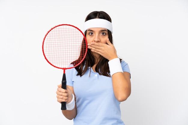 Mulher jovem jogador de badminton sobre parede branca isolada, cobrindo a boca com as mãos