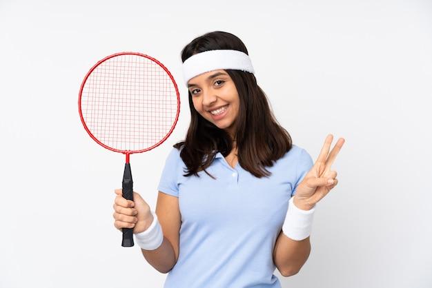 Mulher jovem jogador de badminton sobre parede branca isolada, mostrando sinal de vitória com as duas mãos