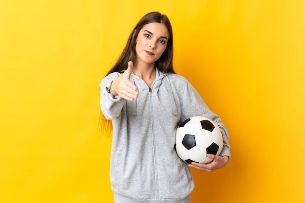 Mulher jovem jogador de futebol amarelo apertando as mãos para fechar um bom negócio