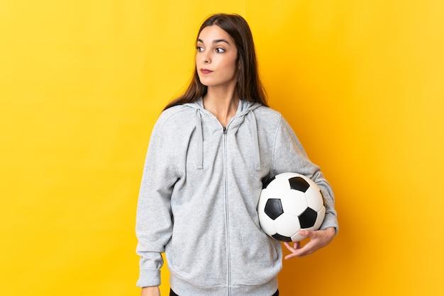 Mulher jovem jogador de futebol amarelo olhando para o lado