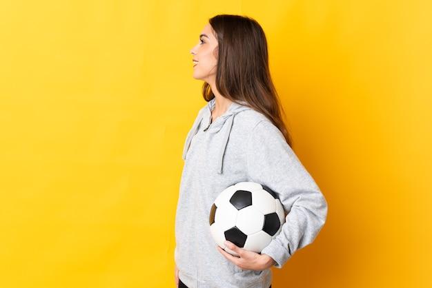 Mulher jovem jogador de futebol amarelo rindo em posição lateral