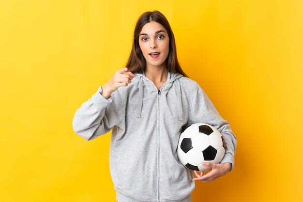 Mulher jovem jogador de futebol amarelo surpreso e apontando para a frente