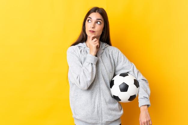 Mulher jovem jogador de futebol amarelo tendo dúvidas