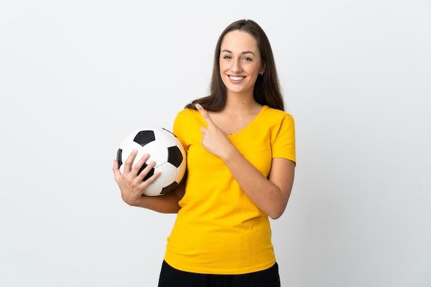 Mulher jovem jogador de futebol americano sobre uma parede branca isolada apontando para o lado para apresentar um produto