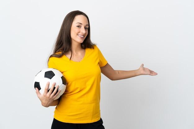 Mulher jovem jogador de futebol americano sobre uma parede branca isolada estendendo as mãos para o lado para convidar para vir