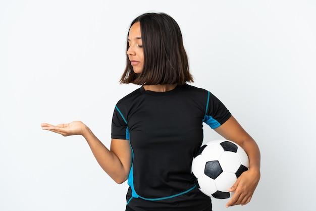 Mulher jovem jogador de futebol em branco segurando copyspace com dúvidas