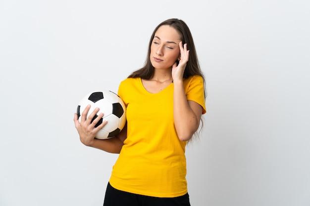 Mulher jovem jogador de futebol em uma parede branca isolada com dor de cabeça
