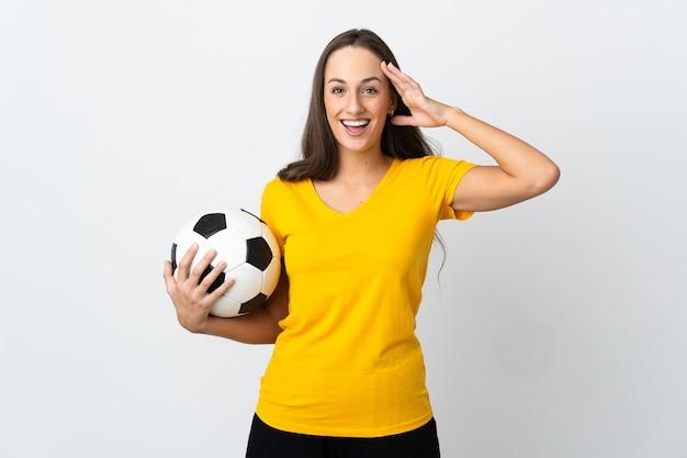 Mulher jovem jogador de futebol em uma parede branca isolada com expressão de surpresa