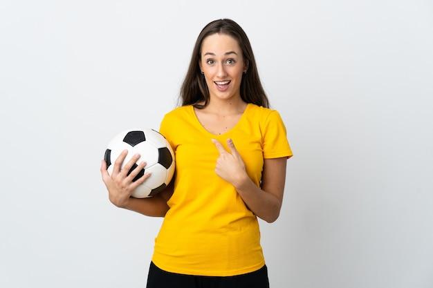 Mulher jovem jogador de futebol em uma parede branca isolada com expressão facial surpresa