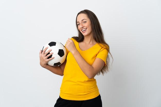 Mulher jovem jogador de futebol em uma parede branca isolada comemorando uma vitória