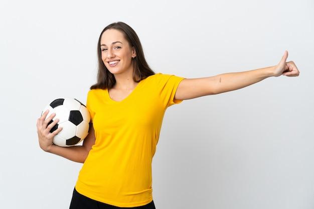 Mulher jovem jogador de futebol em uma parede branca isolada fazendo um gesto de polegar para cima