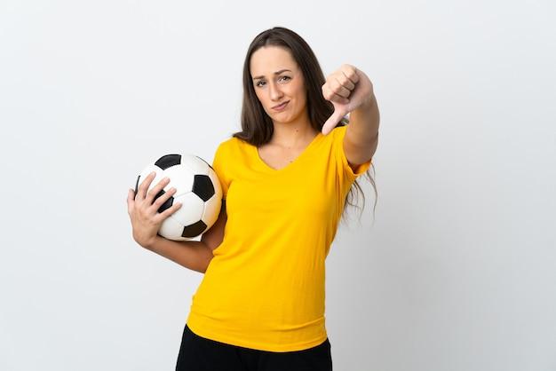Mulher jovem jogador de futebol em uma parede branca isolada mostrando o polegar para baixo com expressão negativa