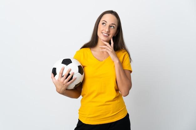 Mulher jovem jogador de futebol em uma parede branca isolada olhando para cima enquanto sorri