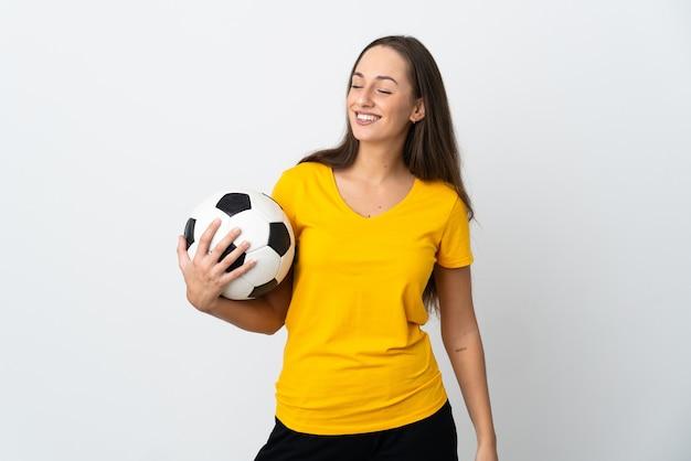 Mulher jovem jogador de futebol em uma parede branca isolada, olhando para o lado e sorrindo