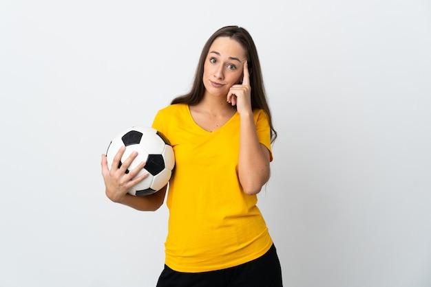 Mulher jovem jogador de futebol em uma parede branca isolada pensando uma ideia