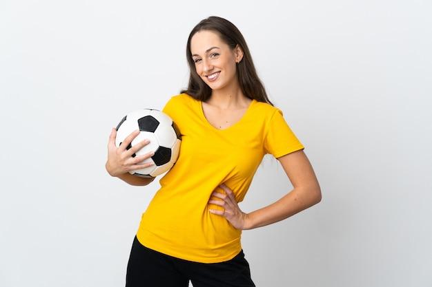 Mulher jovem jogador de futebol em uma parede branca isolada posando com os braços na cintura e sorrindo