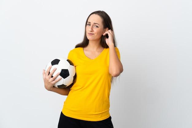 Mulher jovem jogador de futebol em uma parede branca isolada tendo dúvidas