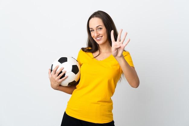 Mulher jovem jogador de futebol feliz na parede branca isolada contando quatro com os dedos