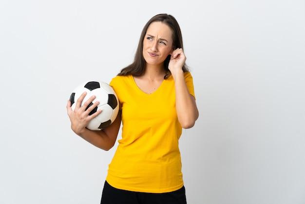 Mulher jovem jogador de futebol frustrada em uma parede branca isolada e cobrindo os ouvidos