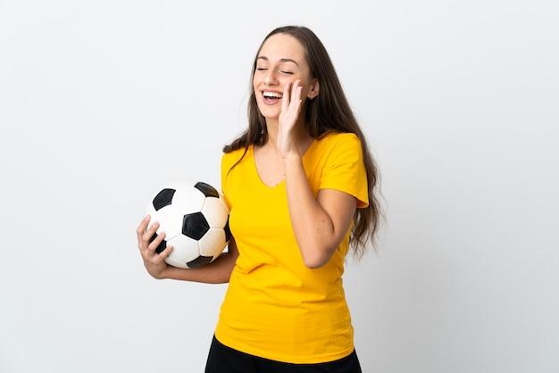 Mulher jovem jogador de futebol gritando em uma parede branca isolada com a boca aberta para o lado