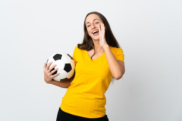 Mulher jovem jogador de futebol gritando em uma parede branca isolada com a boca aberta