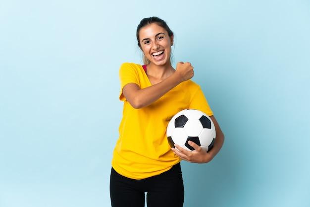 Mulher jovem jogador de futebol hispânico isolada na parede azul comemorando uma vitória