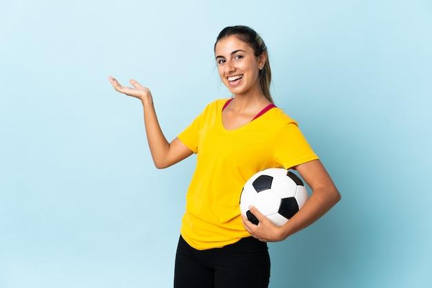 Mulher jovem jogador de futebol hispânico isolada na parede azul, estendendo as mãos para o lado para convidar para vir