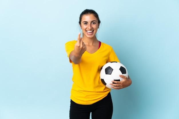 Mulher jovem jogador de futebol hispânico isolada na parede azul fazendo gesto de aproximação