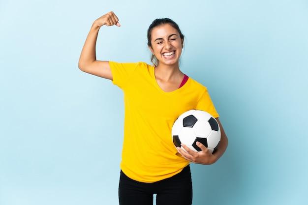 Mulher jovem jogador de futebol hispânico isolada na parede azul fazendo um gesto forte
