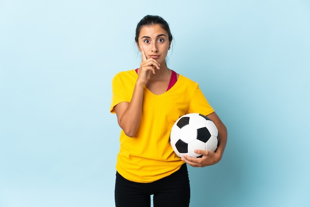 Mulher jovem jogador de futebol hispânico isolada na parede azul, pensando uma ideia