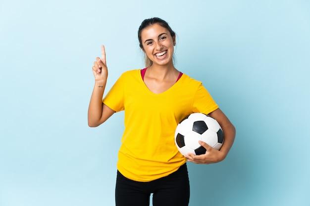 Mulher jovem jogador de futebol hispânico isolado em azul, mostrando e levantando um dedo em sinal dos melhores