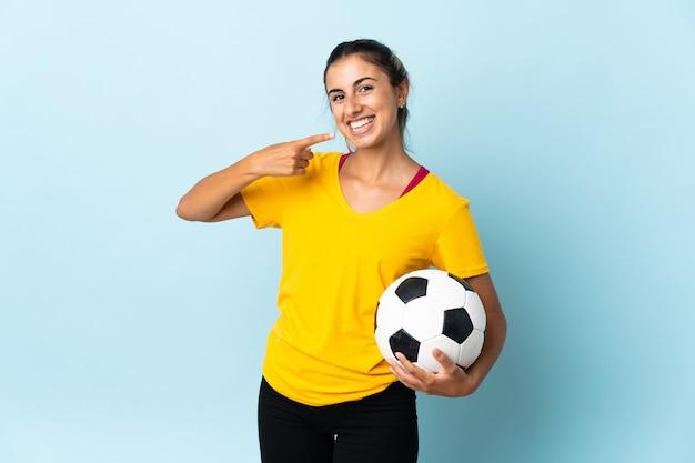 Mulher jovem jogador de futebol hispânico isolado em um fundo azul fazendo um gesto de polegar para cima
