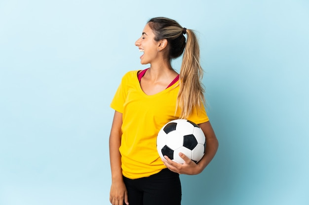 Mulher jovem jogador de futebol hispânico isolado em um fundo azul rindo na posição lateral