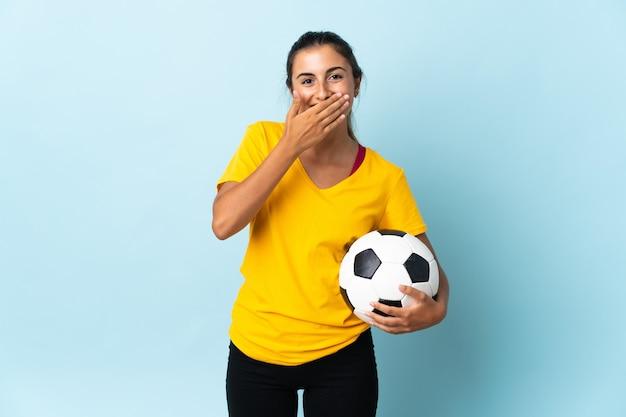 Mulher jovem jogador de futebol hispânico isolado na parede azul, feliz e sorridente, cobrindo a boca com a mão