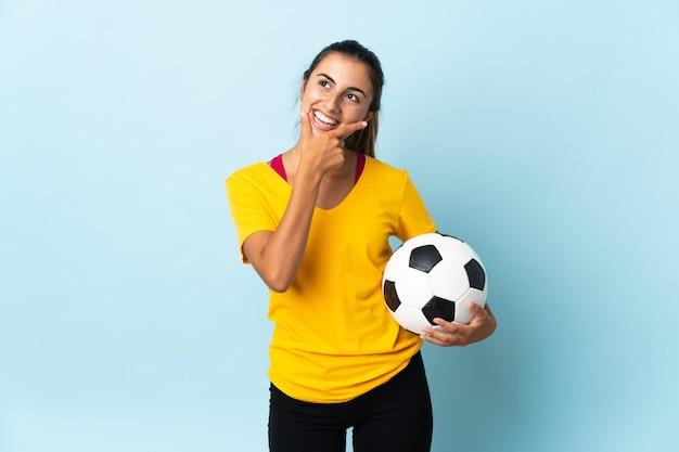 Mulher jovem jogador de futebol hispânico isolado na parede azul feliz e sorridente
