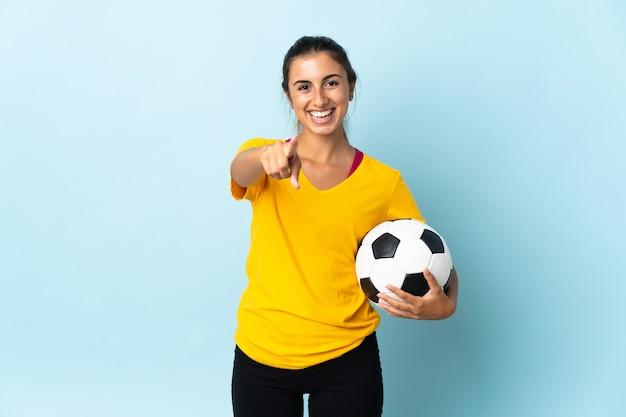 Mulher jovem jogador de futebol hispânico isolado na parede azul surpresa e apontando para a frente