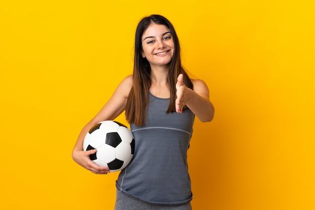 Mulher jovem jogador de futebol isolada em amarelo, apertando as mãos para fechar um bom negócio
