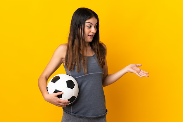 Mulher jovem jogador de futebol isolada em amarelo com expressão de surpresa enquanto olha de lado