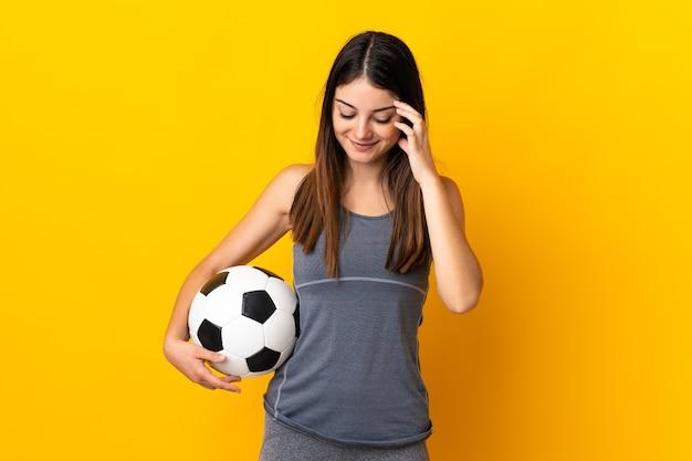 Mulher jovem jogador de futebol isolada na parede amarela rindo