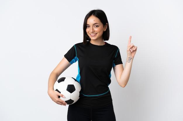 Mulher jovem jogador de futebol isolada na parede branca mostrando e levantando um dedo em sinal dos melhores