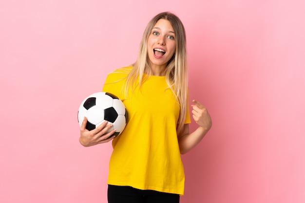 Mulher jovem jogador de futebol isolada na parede rosa, apontando o dedo para o lado