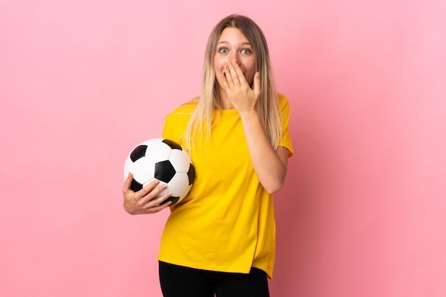 Mulher jovem jogador de futebol isolada na parede rosa com expressão facial de surpresa