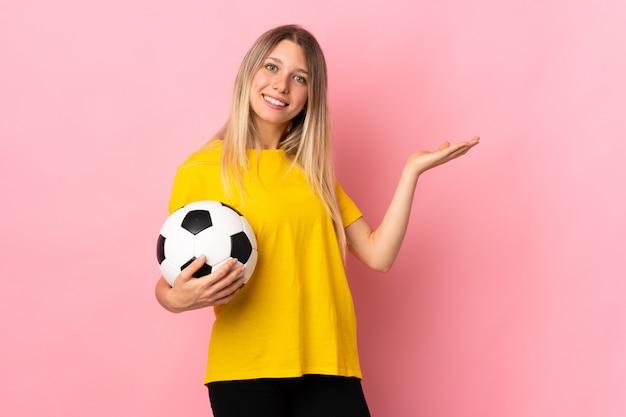 Mulher jovem jogador de futebol isolada na parede rosa, estendendo as mãos para o lado para convidar para vir